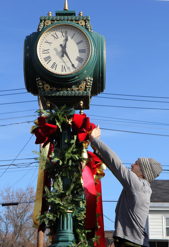 "Matt Hopkins of Hopkins Flowers in Manchester decorates a clock at the Kennebec Savings Bank branch on Main Street in Waterville on Friday. Hopkins and he and several other employees of the flower company have been decorating Kennebec Savings Bank branches throughout central Maine. ""Yesterday we were in Augusta and the day before, Gardiner. We usually start decorating around Thanksgiving,"" Hopkins said."