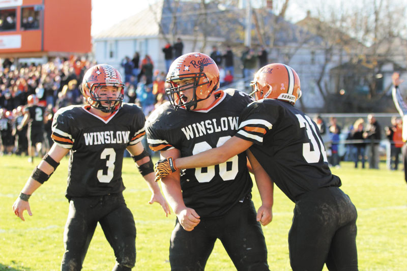 SCORING A REACTION: Winslow High School's Zachary Guptill, center, is congratulated by teammates Ricky Crayton, right, and Dylan Hapwort (3) after scoring a second-half touchdown during the Black Raiders' 17-6 win over Dirigo High School in the Western Maine Class C final on Saturday in Winslow.