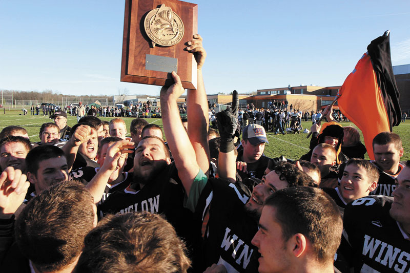 WESTERN C CHAMPS: The Winslow High School Black Raiders celebrate their Western C title after defeating Dirigo High School 17-6 on Saturday in Winslow. Holding the trophy is Brock Deschaine, center, and Jon Farrell, right.
