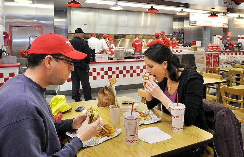 In this April 2011 file photo, Steve St. Jean and Leah Halsey from Portland taste the famous cheeseburgers and fries at the Five Guys Grand Opening at 425 Fore Street.