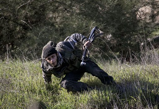 A Free Syrian Army fighter takes cover Saturday during heavy clashes with government forces at an infantry base besieged by the rebels north of Aleppo. Free Syrian Army fighters took control over the military academy after battling government forces for several hours.
