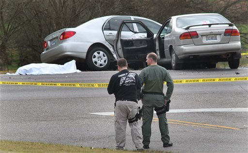 Authorities stand watch over a scene where a body lies covered with a sheet on Highway 78 in Oxford, Ala., on Saturday. Police officers in eastern Alabama shot an assailant armed with an AK-47 assault rifle toward the end of a pursuit that left several people injured, including Heflin police officer Jackie Stovall, authorities said.