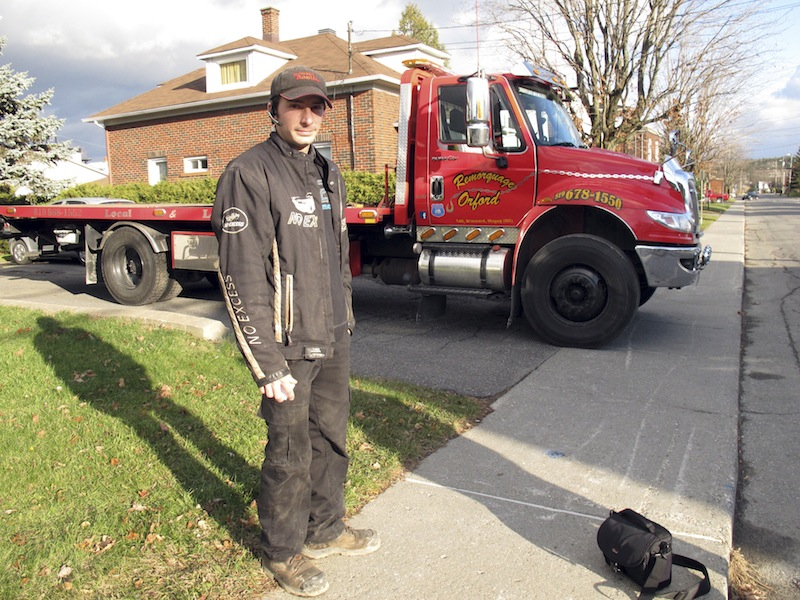 In this Nov. 13, 2012 photo, Nicholas Dostie stands in front of his tow-truck in Magog, Quebec, that he said he used to tow a van in which about a dozen men, women and children entered Canada illegally from the United States and applied for political asylum. Canadian immigration officials on Wednesday, Dec. 5, 2012 said a Romanian smuggling ring has been bringing Gypsies into the U.S. through Mexico in order for them to eventually gain asylum in Canada. (AP Photo/Wilson Ring)