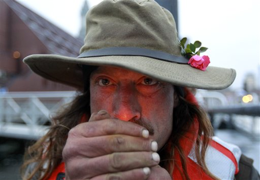 Michael Richard Smith lights a cigarette while speaking with members of the media on a wharf in Boston Harbor on Tuesday. On Monday night, Smith tied up and slept on a floating dock about 100 yards offshore from the New England Aquarium.