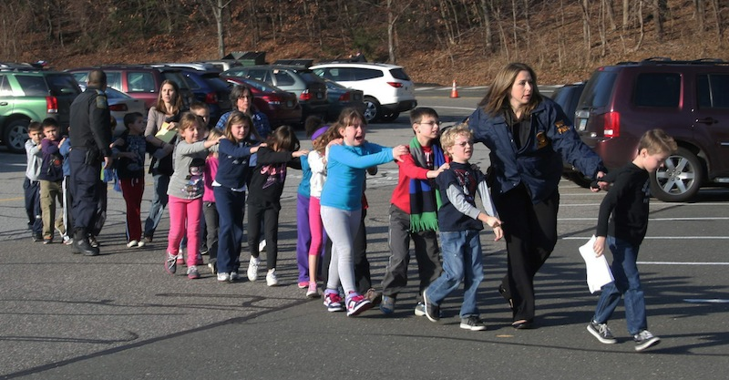 In this Friday, Dec. 14, 2012 file photo provided by the Newtown Bee, Connecticut State Police lead a line of children from the Sandy Hook Elementary School in Newtown, Conn. after a shooting at the school. The private equity firm Cerberus will sell its stake in a firearms company that produced one of the weapons believed to have been used in the shootings at the elementary school, calling it a