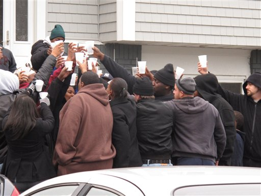 Friends and relatives of Jovan Belcher drink a toast outside the player's home on Saturday in West Babylon, N.Y.