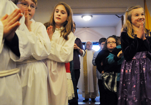 Children line up to lead Fr. George Hickey, center, into the Christmas Eve Mass at Sacred Heart Catholic Church in Hallowell on Monday.