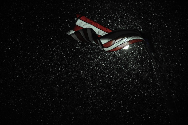 Snow is illuminated by a street light as an American flag blows in the wind during a winter storm Wednesday, Dec. 26, 2012, in Paducah, Ky. An enormous storm system that brought snow and sleet to the nation's midsection -- and tornadoes to the Deep South -- is now moving its way toward the Northeast. (AP Photo/Stephen Lance Dennee)