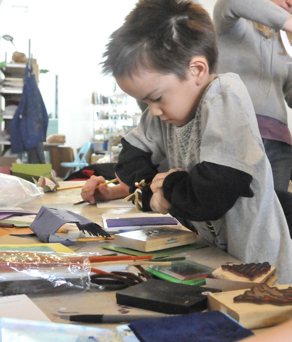Bryce Keith, 6, selects a Christmas tree stamp during a holiday card-making workshop at Common Street Arts in Waterville on Saturday.