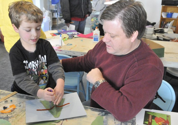 James Stewart, 44, of Oakland, and his son, Lukas, 6, work on making a Christmas tree pop-up card during a holiday card-making workshop at Common Street Arts in Waterville on Saturday. The workshop was sponsored by Common Street Arts and the Colby College Art Museum.