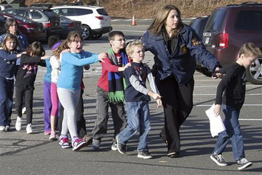 In this photo provided by the Newtown Bee, Connecticut State Police lead children from the Sandy Hook Elementary School in Newtown, Conn., following a reported shooting there on Friday.