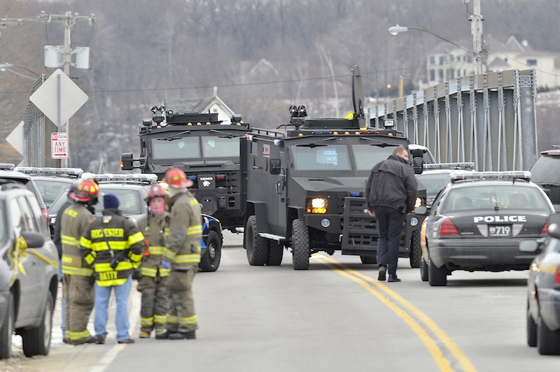 Swat teams appear at the scene of a fire in Webster, N.Y., Monday, Dec. 24, 2012. Police in New York state say a man who killed two firefighters in a Christmas Eve ambush had served 17 years for manslaughter in the death of his grandmother. (AP Photo/Messenger Post Media, Seth Binnix)