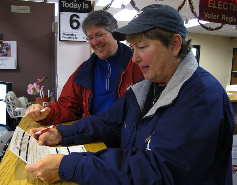 Deb Dulaney, left, watches as her partner, Diane McGee, fills out paperwork for their marriage license at the Thurston County Auditor's office at the courthouse, on Thursday, Dec. 6, 2012, in Olympia, Wash. Washington state's new voter-approved gay marriage law took effect Thursday, and couples across the state began picking up licenses and can start marrying as soon as Sunday. (AP Photo/Rachel La Corte)
