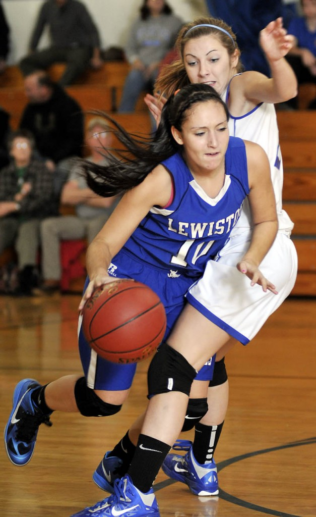 Staff photo by Andy Molloy PASSING THROUGH: Erskine Academy's Taylor Boucher, right, guards Lewiston High School's Jannessa Talarico Tuesday night in South China. Lewiston beat Erskine 61-40.