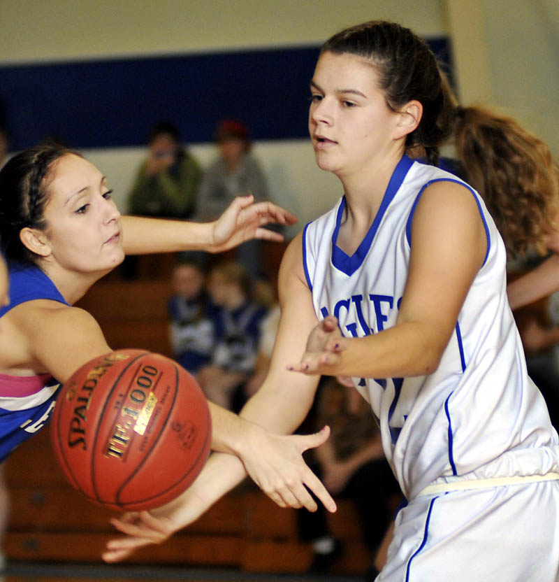 Staff photo by Andy Molloy DISHING IT OFF: Erskine Academy's Hannah Bridges, right, pitches the ball away from Lewiston High School's Jannessa Talarico Tuesday in South China. Lewiston won the contest 61-40.