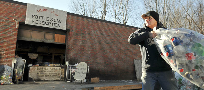 Steve Hodgkins tosses bottles into a truck Monday at his Winthrop redemption center, M.T. Bottle Co. The firm is moving to a new location.