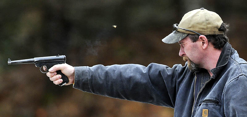 """Jeffrey Fortin, of Augusta, fires a pistol Saturday, at a range in Augusta. Fortin, who recently purchased an assault rifle, said the recent surge in gun sales is from fear. """"Everybody is scared,"""" Fortin said."""
