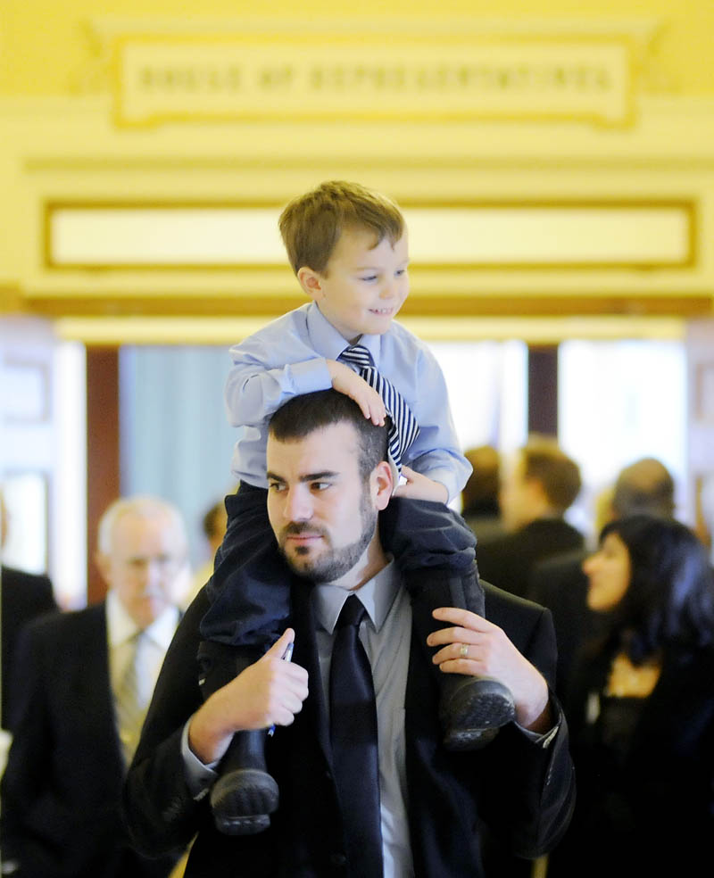 Rep. Jeff McCabe, D-Skowhegan, carries his son, Finnegan, 4, Wednesday, Dec. 5, before being sworn in for a new term in the House of Representatives at the State House in Augusta.