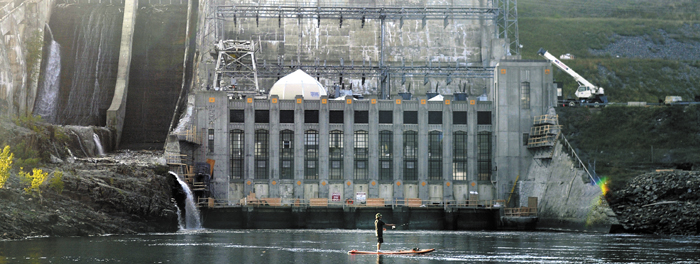 An angler casts for a fish beneath Wyman Dam in Moscow this summer. The 84-megawatt dam, owned by NextEra Energy Partners, is being sold, along with a portfolio of Maine dams, to Brookfield Renewable Energy Partners, a Canadian firm.
