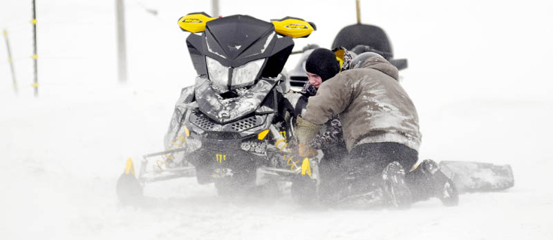 Alex, left, and his father, Mike McPherson, inspect the engine of a snowmobile Sunday, in Farmingdale. The men were taking a run together to celebrate Alex's 17th birthday when his sled developed some engine problems. The snow machine was driven to a cousin's barn to inspect the plugs.