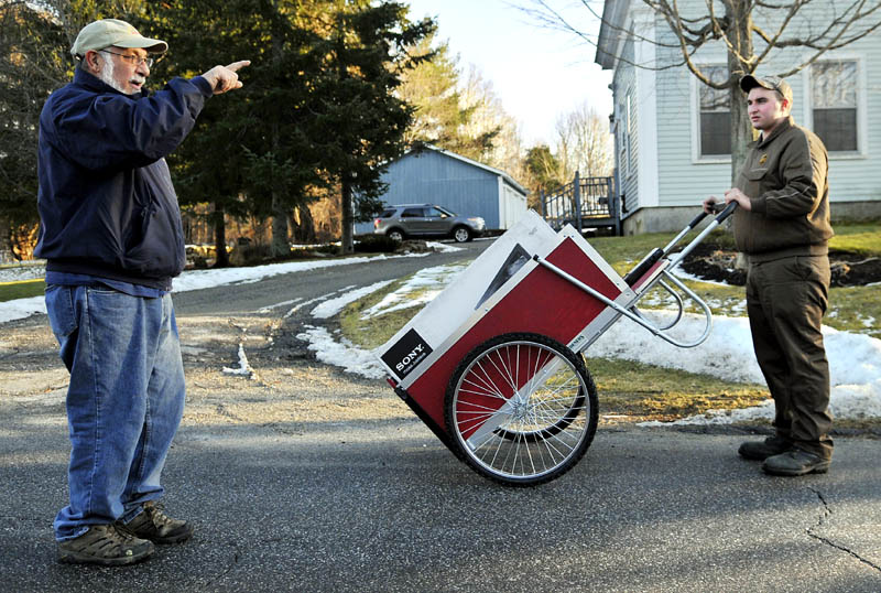 """George Sparacio, left, gives UPS driver helper Joseph Ouellette some directions Thursday in Gardiner. Ouellette said he covers several miles a day delivering packages with the push cart. """"It's good exercise,"""" he said of his part-time job. Sparacio was walking near his home."""