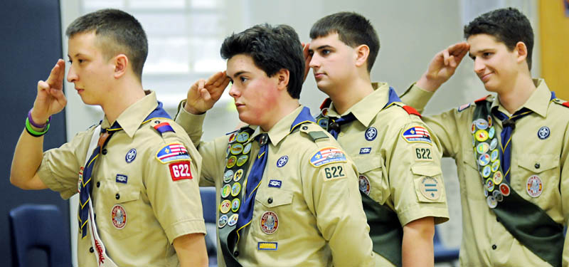 Nick Neuhaus, left, Tucker Whitman, Tommy Lanphear and Alec Daigle salute the flag Sunday, during their Eagle Court of Honor by Boy Scout Troop 622 in Manchester. The teenagers were recognized at the Manchester Elementary School after each completed lengthy community projects and were elevated to the ranks of Eagle Scout.