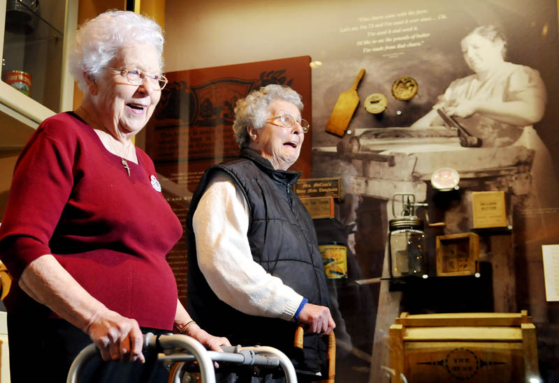 Jeanne Chamberland, left, 88, of St. Agatha and her sister, Lillian Bussier, 84, of Lewiston, laugh after viewing a photo Friday of their mother, Emma Gagnon, pouring buttermilk. The photo, captured by Farm Security Administration photographer John Collier Jr. while documenting the Gagnon family's potato farm in Frenchville, is on display at the Maine State Museum in Augusta. Gagnon, a mother of 11 children, passed away from tetanus at the age of 42, two years after the photo was created. It was the first time Chamberland saw the photo.