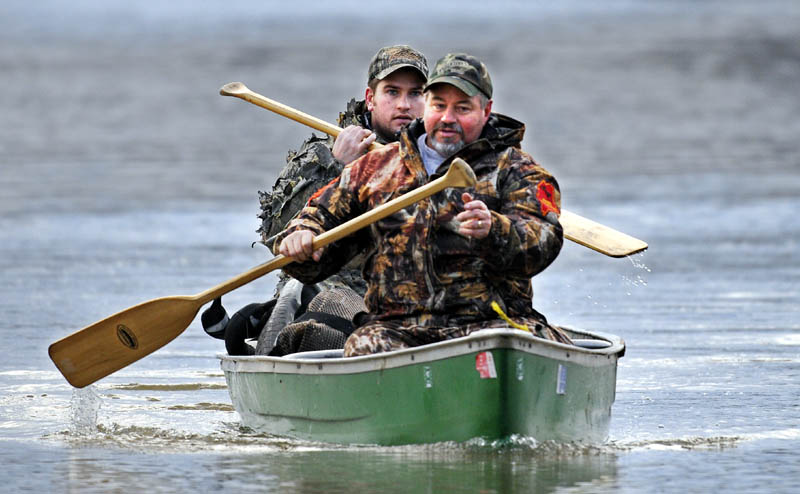 Steve Swindells, right, of Smithfield and his son, Matt of Gardiner, return to their blind in Chelsea on Saturday, while waterfowl hunting at dawn on the Kennebec River. The men said they spotted flights of ducks and geese but didn't harvest any birds.