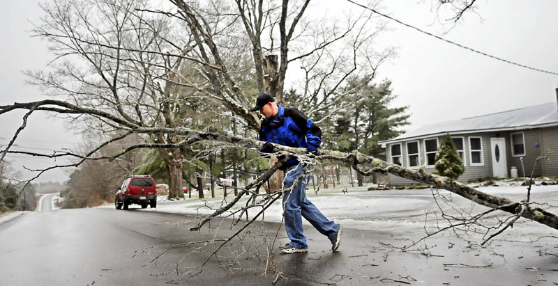 """John Smith moves a limb Monday from the lawn of his mother-in-law's Augusta home. Smith said the late fall weather is """"not bad this year."""""""