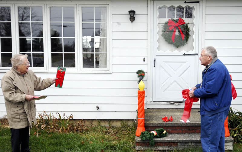 "Lora Briggs, 86, directs her son-in-law, Howard Cooke, how to display ribbons recently at her Monmouth home. Briggs said that Cooke mows, trims, and hangs the holiday ornaments with only limited supervision. ""He's really improved the last 10 years,"" she joked."