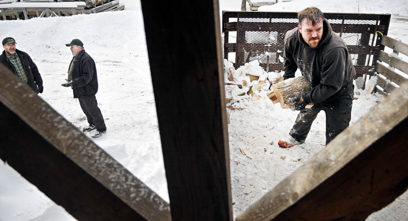 Mike Baker, left, confers with Paul Peaslee Sr., on Sunday as his son, Paul Peaslee Jr., unloads several cords of firewood at Baker's Smelt Camps in Pittston. The elm and ash keep the shacks that sit on the frozen river warm for winter anglers, Paul Peaslee Jr. said. Baker said that camps, which burn about 25 cords a winter, should be opening next week.
