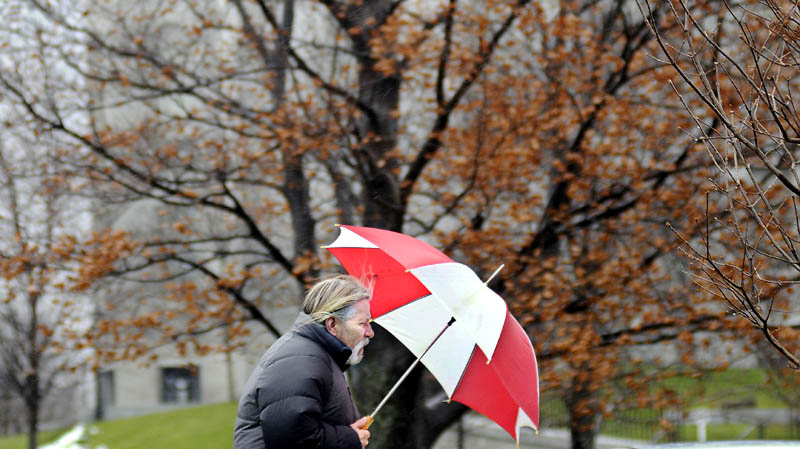 Dana Philippi walks into the rain Friday in Augusta. Philippi was returning to his office in a heavy rain.