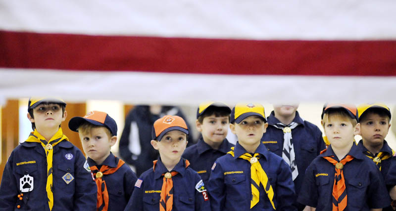 Members of Cub Scout Pack 222, of Palermo, observe soliders with the Maine Army National Guard's Maine Military Funeral Honors Program folding the U.S. flag Tuesday, at the Augusta State Armory. After watching the soldiers present the colors, the Scouts practiced proper flag etiquette under the supervision of the Guardsmen, who provide honor burials for veterans.