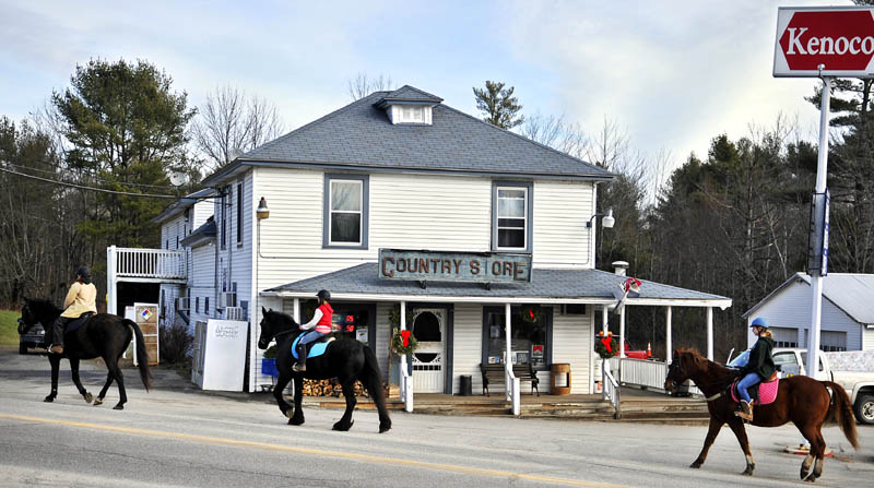 Jana Christman, left, leads her friend, Emily Boedeker, 11, center, and daughter, Emma Christman, 12, past the Litchfield Country Store on horseback Sunday. The trio were riding along the edge of the road with their steeds before taking to trails through the woods to loop back to their Litchfield homes.