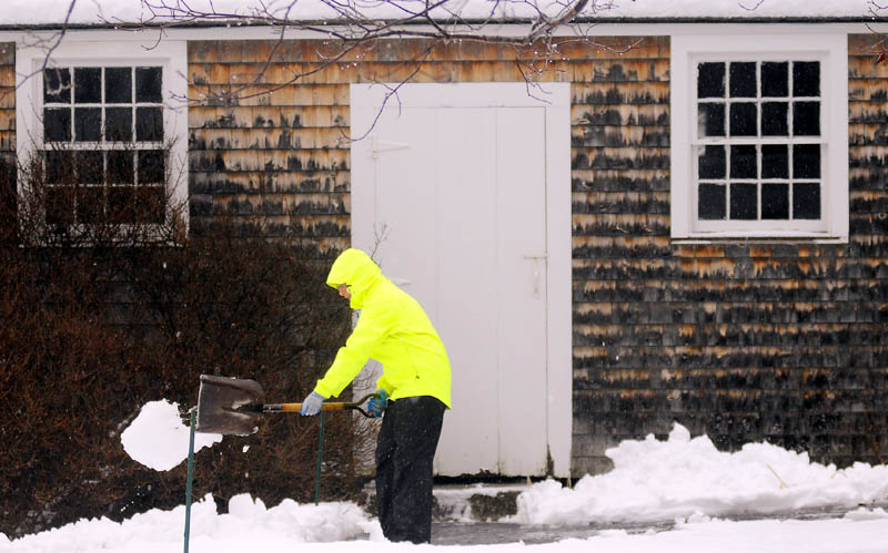 """Nancy Russell, of Readfield, moves slush away from the walkway of her shed Tuesday, as rain descends upon the fresh coat of snow. """"It's a lovely day to shovel,"""" Russell remarked. """"It will all turn to ice if I don't shovel it now."""""""