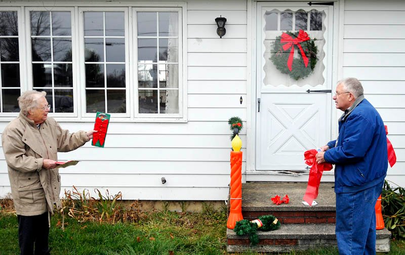 """Lora Briggs, 86, directs her son-in-law, Howard Cooke, how to display ribbons recently at her Monmouth home. Briggs said that Cooke mows, trims, and hangs the holiday ornaments with only limited supervision. """"He's really improved the last 10 years,"""" she joked."""