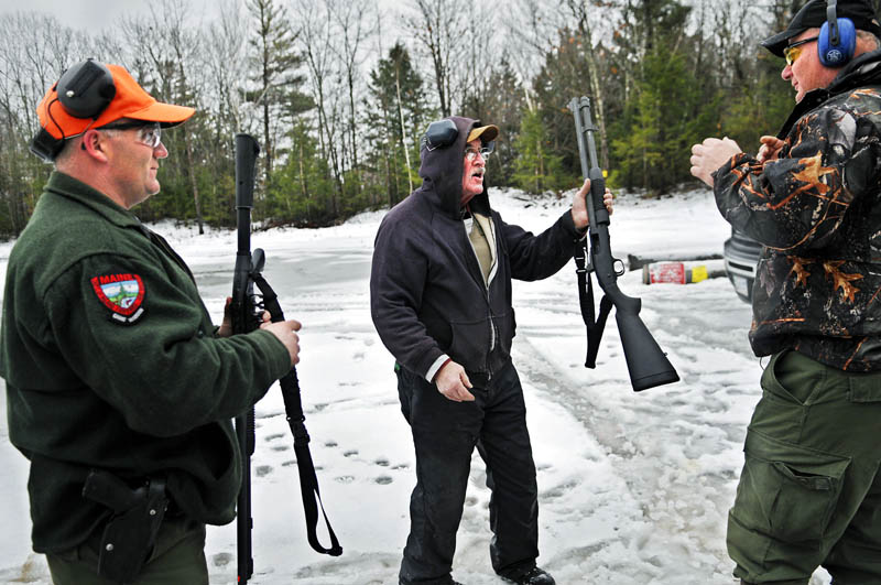 Deputy Game Warden Don Gray, center, hands a shotgun to District Game Warden Norman Lewis, right, as he and acting Sgt. Dave Chabot, left, prepare to fire the weapons Wednesday at a range in Augusta. The state wilderness law enforcement officers qualify on sidearms and shotguns twice a year. Gray, who retired from the warden service as a sergeant after four decades of service, still serves as a deputy warden in the Bethel area.