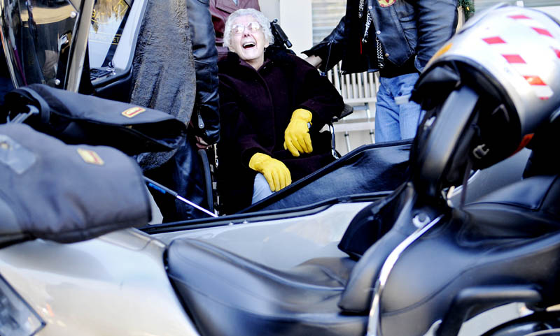 """Olive Taverner laughs Wednesday after dismounting the sidecar of a motorcycle following, a ride in 20 degree F temperatures through Augusta. The 91-year-old said the bike ride, courtesy of the Combat Vets Motorcycle Association, was on the bucket list she composed upon retiring as a teacher in 1986. The resident of Gray Birch Long Term Care in Augusta said the only wish she has to left to complete on the list is a helicopter ride. The side car journey was, she said, """"just wonderful."""""""