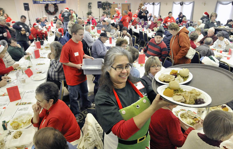 Stacey Hachey, center, delivers a tray of turkey dinners to tables at the Central Maine Family Christmas Dinner at the Elks lodge in Waterville on Tuesday. More than 500 dinners had been served by noon.