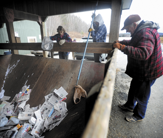 Reggie Lane, center, an employee at the Wilton Transfer Station, fishes a plastic bag out of the single-stream dumpster as Lawrence Farrington, right, and his wife, Marcella, left, throw away recylable materials on Wednesday. Although the new recycling method is single-stream, some materials need to be excluded, such as plastic shopping bags.