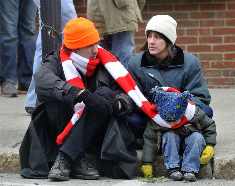 Steven Woodman shares his scarf with his son Tristram, 3, as mother Darlene Woodman sits in the background, at the Chester Greenwood Day parade in downtown Farmington Saturday.