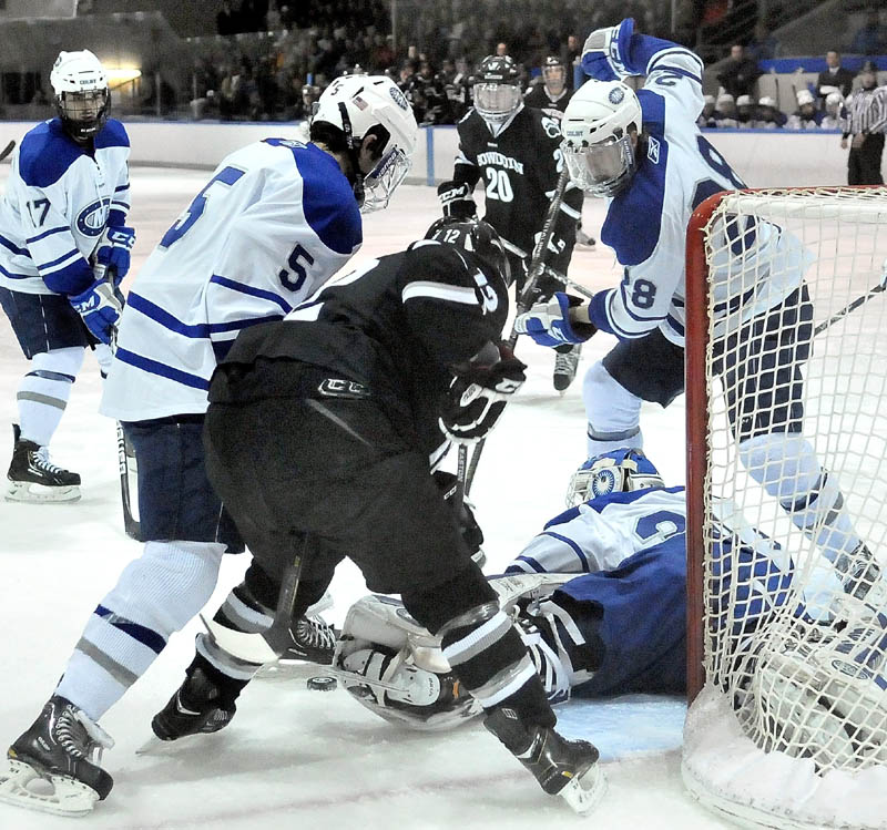 Colby College goalie Jordan Nathan, 30, tries to make a save as teammates Brendan Cosgrove, 5, left, and Scott Harff, 28, right, scrap for the puck with Bowdoin College's Harry Matheson, 12, center tries to score in the first period at Alfond Arena at Colby College in Waterville on Saturday.