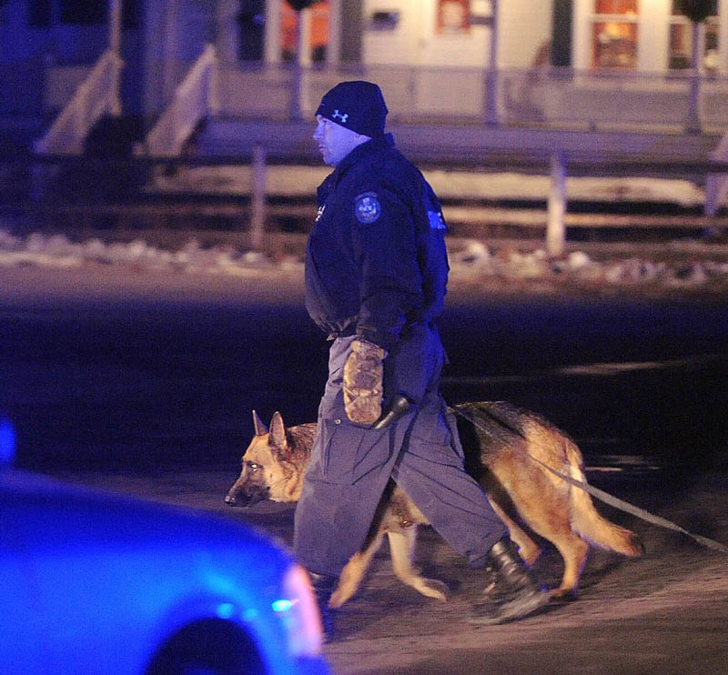 State police Trooper Rick Moody and his dog, Kushel,search for a man who robbed the Franklin Savings Bank in Skowhegan Thursday night.