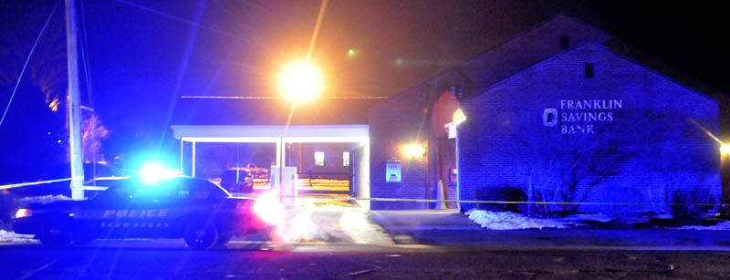 A Skowhegan Police cruiser sits parked next to Franklin Savings Bank on Madison Avenue after a robbery on Thursday.