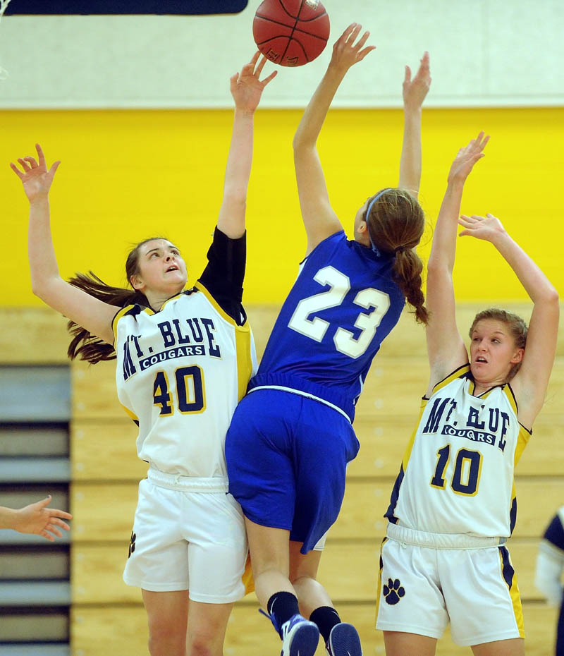 Mt. Blue High School defenders Addie Brinkman, eft, and teammate Jaycee Jenckes, right, try to block a shot by Lawrence High School's Paige Belanger, in the second quarter Friday at Mt. Blue High School in Farmington.