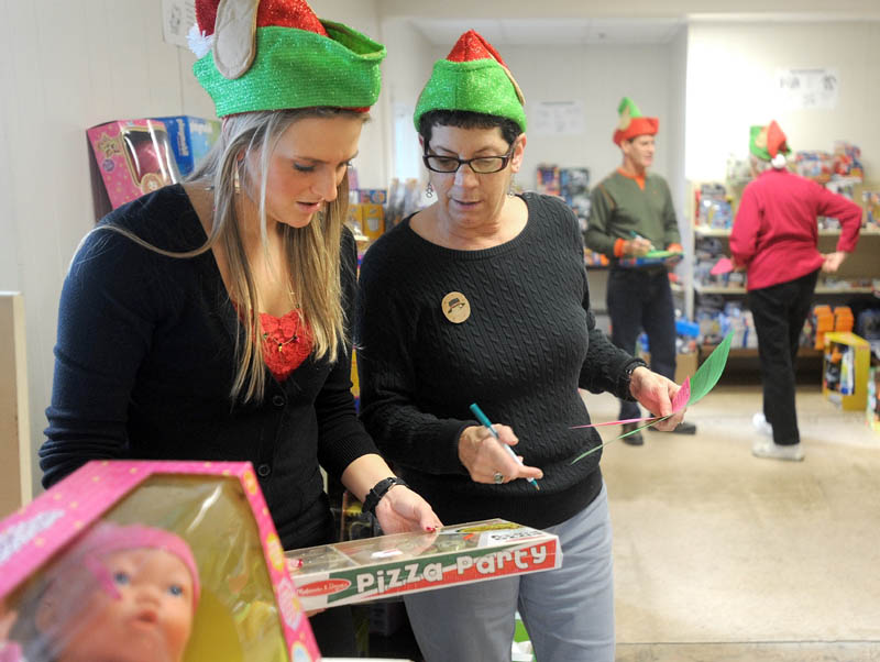 Kasie Flowers, left, and Tina Carter, right, of the Waterville Housing Authority, pick a toy from the shelf to pack inside a gift box, to be distributed to disadvantaged children in the area for the holidays, at the Maine Children's Home for Little Wanderers in Waterville on Nov. 29.