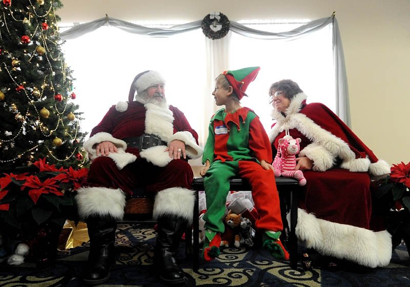 Santa Claus listens to honorary elf, Zachary Wentworth, at the Central Maine Family Christmas Dinner at the Elks lodge in Waterville on Tuesday.