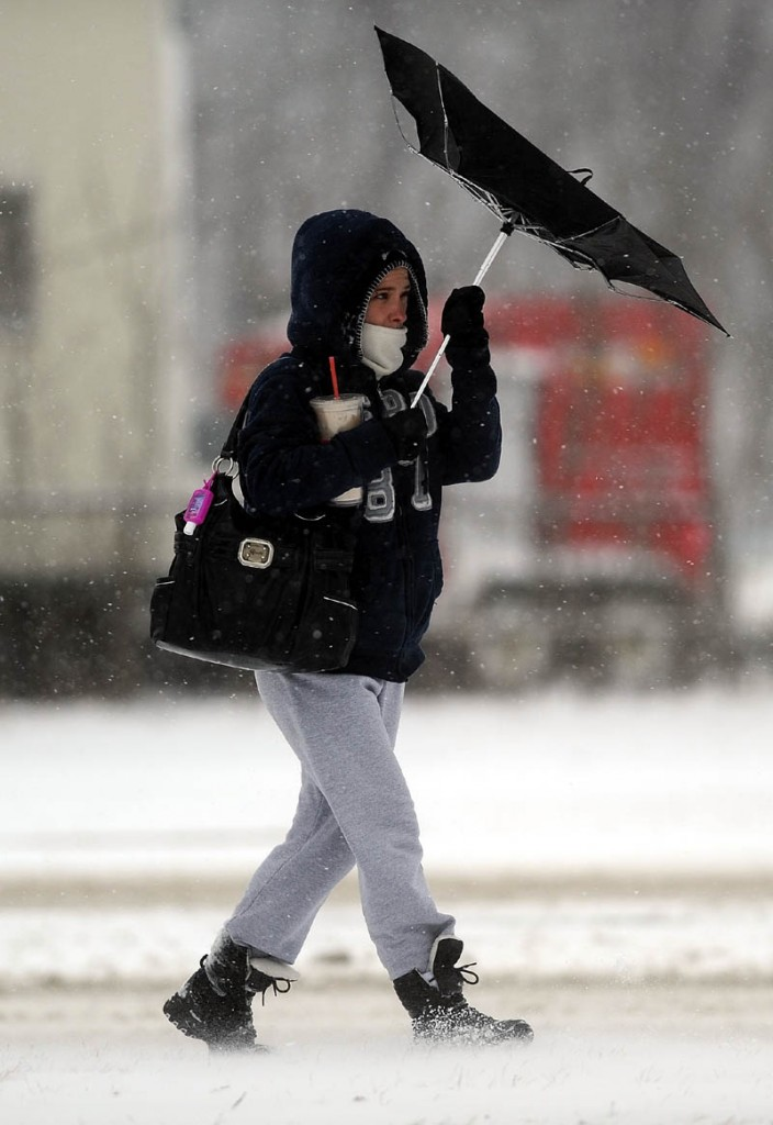 Staff photo by Michael G. Seamans Elizabeth Lawson, of Waterville, struggles with her unbrella as she is pelted with snow and high winds on her way to Dunkin' Donuts on College Avenue in Waterville Thursday. Central Maine is expected to see 12 - 18 inches of snow before the storm moves through by Friday, according to the National Weather Service.