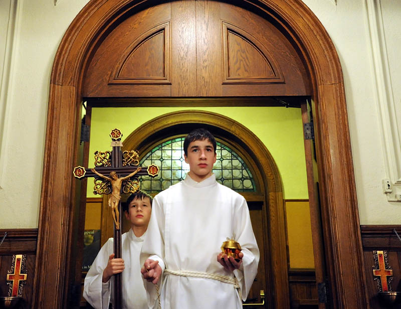 William Couture, 15, front, and his brother, Edmund, 11, both altar servers, prepare for the beginning Midnight Mass at Sacred Heart Catholic Church on Pleasant Street in Waterville on Tuesday.