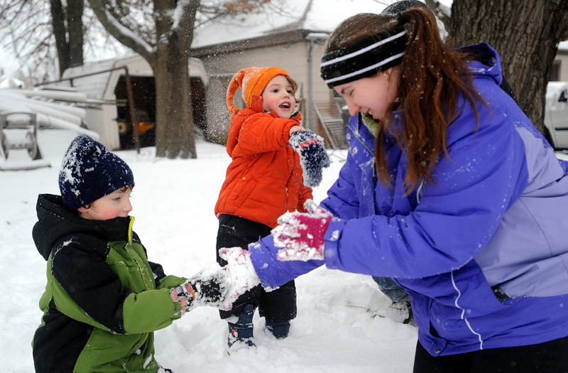 J.J. Burns, 2, center, pelts his mother, Melissa, with a snowball as she helps his big brother, Ian, 5, make a snowball during a winter storm on St. John Street in Winslow on Thursday.